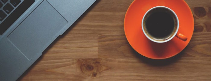 Overhead view of a laptop computer and orange saucer full of coffee, both sitting on a wooden table.