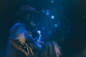 A guitar player under blue lights on a stage.