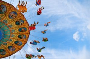 Group of fair-goers flying high in a carnival ride.