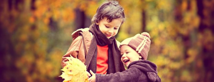 Two young boys playing with autumn leaves in a park.