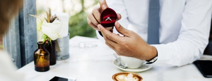 Man opening a heart-shaped box with an engagement ring inside over coffee.
