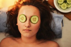 Woman's face with cucumber slices over her eyes.